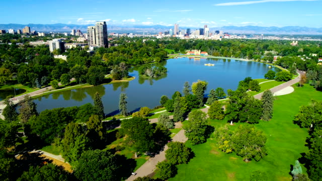 vídeos de stock e filmes b-roll de large pond reflecting the denver colorado skyline cityscape and surrounding trees at city park aerial drone view - public park