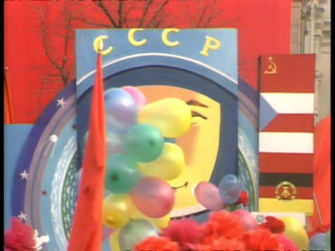 CU Large poster of cosmonaut moving right, balloons in foreground, Moscow