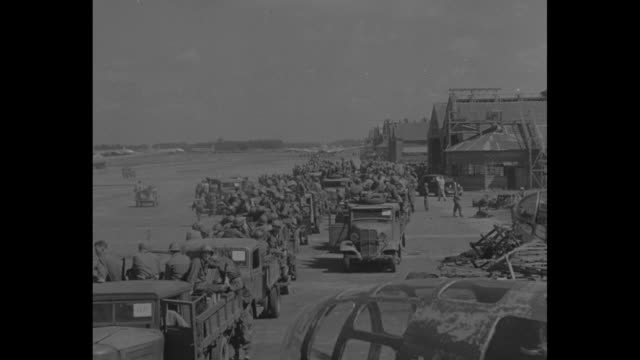 Large ramshackle cars and trucks parked at airfield / soldiers march on airstrip / wrecked Japanese plane and hangars with mass of Americans gathered...