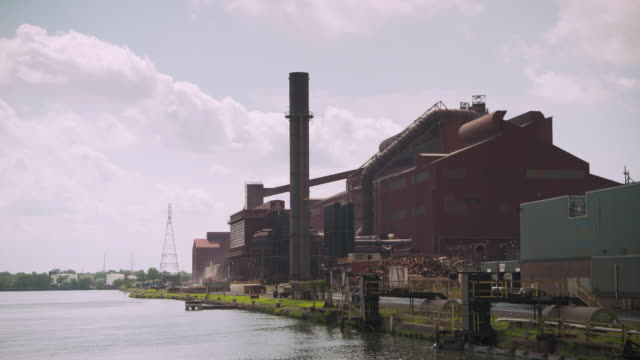A large red factory with smoke stack is situated next to a river, Dearborn, Michigan, USA.