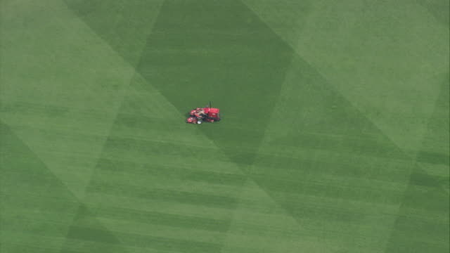 AERIAL Large, red riding lawn mower cutting the grass field at the empty Fenway Park baseball stadium / Boston, Massachusetts, United States