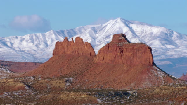Large rock formations stand in the foreground of snow covered mountains.