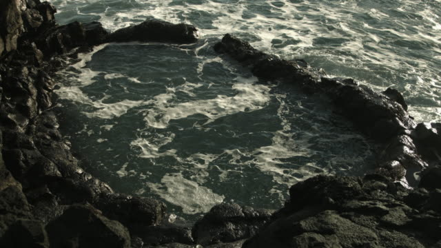a large rockpool fills with seawater on the reykjanes peninsula in iceland.  - gezeitentümpel stock-videos und b-roll-filmmaterial