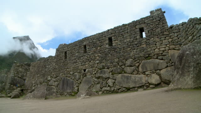 large rocks give way to a stone wall in the ruins of machu picchu. - stone wall stock videos and b-roll footage