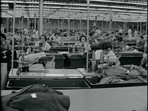 large room w/ women working at sewing machines. vs rows of sewing machines w/ women working, bins for completed piece work on other side of table.... - made in usa点の映像素材/bロール
