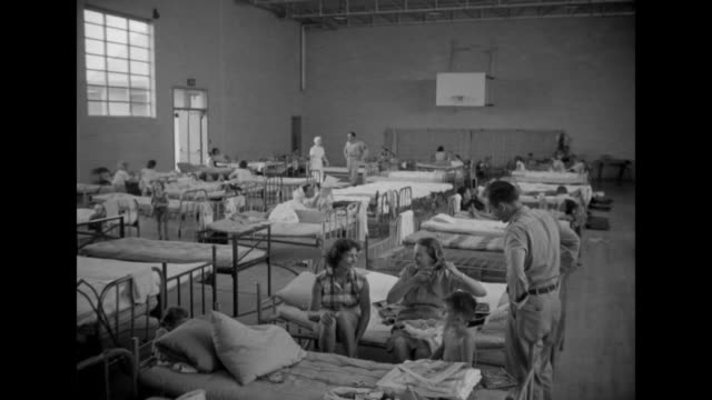 vídeos de stock e filmes b-roll de ms large room with cots for people displaced by floods / ms two babies lying on bed two toddlers on bed next to them / ms doctor examines little girl... - cama de campanha