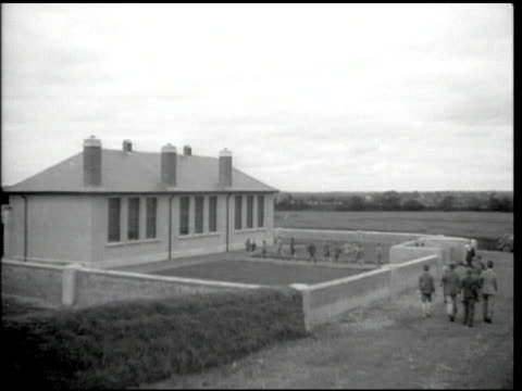 Large school building w/ walkway in walled yard children walking to country school entrance on path some barefooted several in shorts
