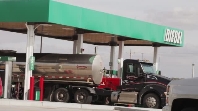 large semi-truck tanker drives away from the diesel fill station at a truck stop. - petrol station stock videos & royalty-free footage
