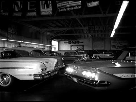 stockvideo's en b-roll-footage met large service garage of chevrolet dealership - mechanics walk about, cars parked in bays, one car on hydraulic lift; chevy impala reverses into frame... - chevrolet