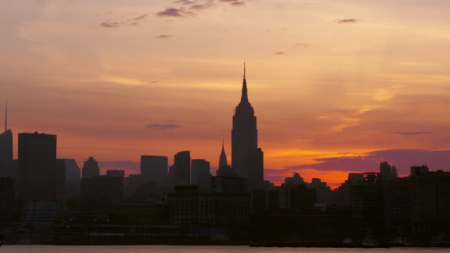 Large ship slowly coasts along Hudson River in front of Empire State Building at dawn