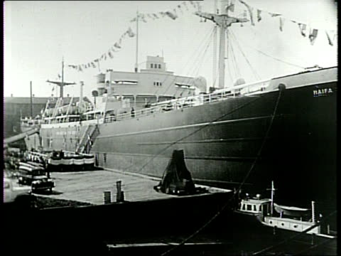 a large ship ss haifa sits at dock / people gather around the ship / a large crowd sits in chairs in front of the ship on the dock during the... - haifa video stock e b–roll