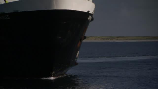 a large ship turns in waters near a shore. - 船体点の映像素材/bロール