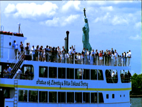 Large sightseeing ferry boat sails past Statue of Liberty against blue sky