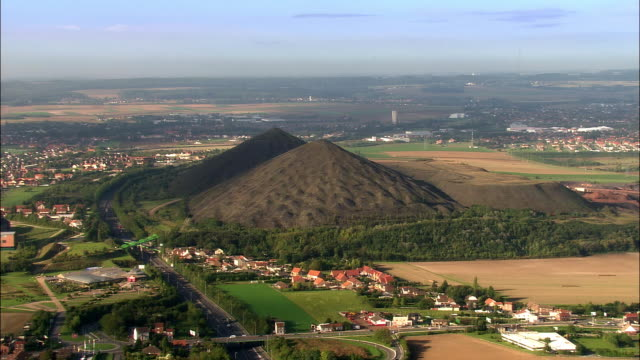 aerial large slag heaps with traffic passing by on road/ lens, france - lens pas de calais stock videos & royalty-free footage