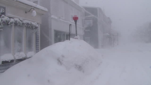 large snow mounds and snow drifts line main street in plymouth mass during a blizzard - haufen stock-videos und b-roll-filmmaterial