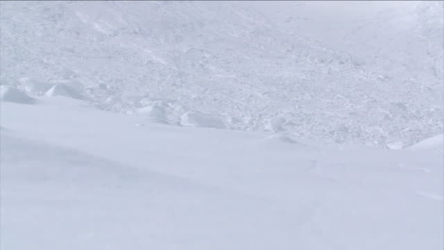 a large snowball rolls down a hillside past the remains of an avalanche. - rolling stock videos & royalty-free footage