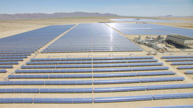 WS AERIAL POV Large solar array in desert valley with mountain ranges in distance / California, United States