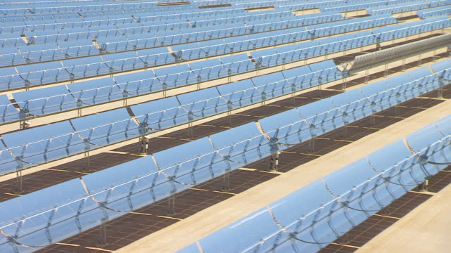 WS AERIAL POV Large solar array reflectors in desert valley / California, United States