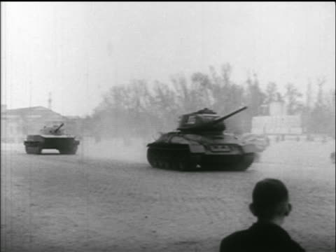 PAN large Soviet tank speeds through square past camera / Hungarian uprising