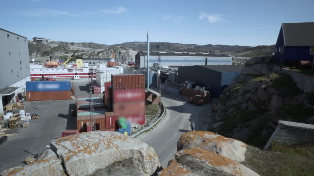 vídeos de stock, filmes e b-roll de large stack of shipping containers in a loading area by the ilulissat harbor - disko bay, greenland - grande angular