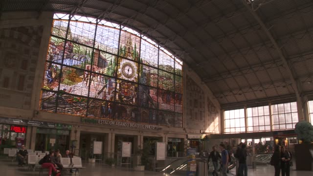 a large stained glass window overlooks commuters at the bilbao-abando train station. - spanish basque country stock videos and b-roll footage