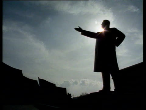 Large statue of Kim II Sung with arm extended with sun setting behind