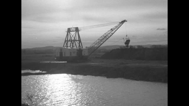 large steam shovel sitting next to river being used to scoop up earth from river and move it to land / note: exact month/day not known - rhone river stock videos & royalty-free footage