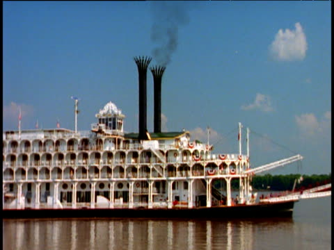 Large steamboat sails along Mississippi river with smoking chimneys and red paddle