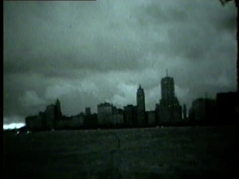 wgn large storm clouds roll over the chicago skyline as people cover their faces from the wind in july 1954 - 1954 bildbanksvideor och videomaterial från bakom kulisserna