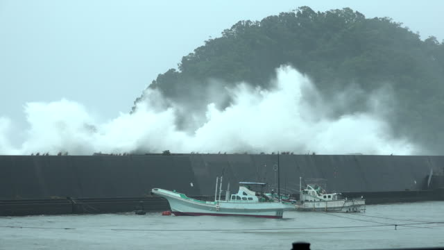 vídeos de stock e filmes b-roll de large storm waves crash over sea wall as typhoon cimaron hits the coast of japan - divisa