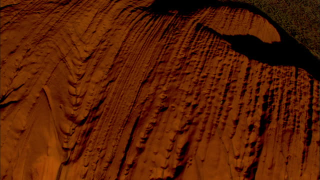 large striations characterize ayers rock. - エアーズロック点の映像素材/bロール