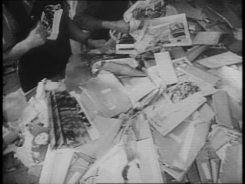 large striped bags sit on the ground / workers sort through letters sitting at several tables while in the background someone turns a striped bag... - anno 1941 video stock e b–roll