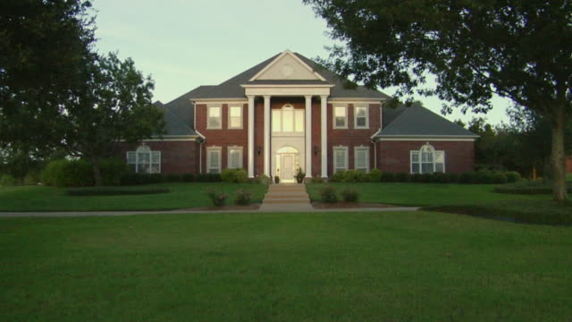 ws pan large suburban home with columns and lawn/ temple, texas - colonna architettonica video stock e b–roll