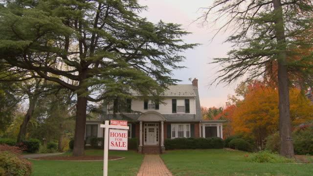 ws, td, large suburban house with 'for sale' sign in front yard, richmond, virginia, usa - 売り出し中点の映像素材/bロール