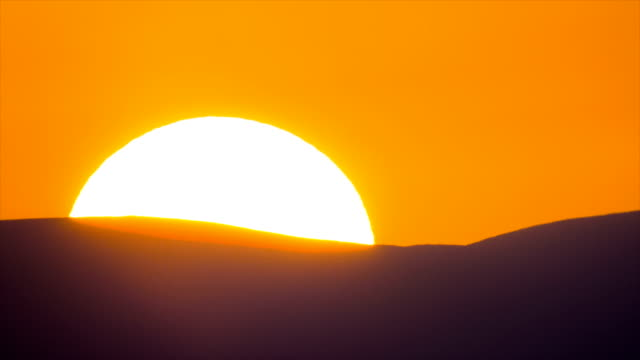 large sun rising and unveiling slowly above horizon, behind horizontal mountain ridge, with warm orange tones. - awe stock videos & royalty-free footage