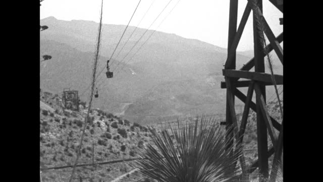 vídeos y material grabado en eventos de stock de large suspended buckets move up down along a cableway system / donkeys with heavy boxes trudge along in a rocky desert as one handler walks behind... - cable de acero
