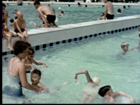 1957 MONTAGE Large swimming pool filled w/ adults + kids People sitting at tables w/ umbrellas w/ pool in background. Country club / Singapore / AUDIO