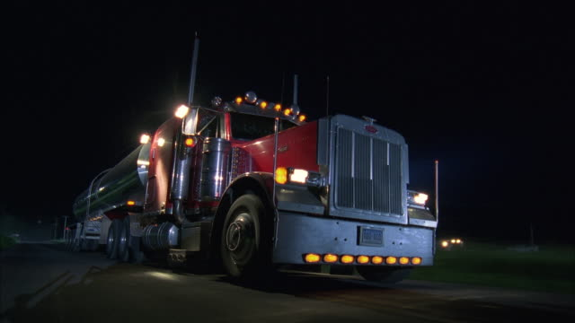 ms large tanker truck driving along rural highway at night - articulated lorry stock videos & royalty-free footage