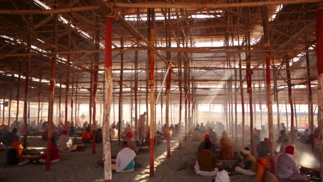 Large temporary structure shading groups of people from the sun