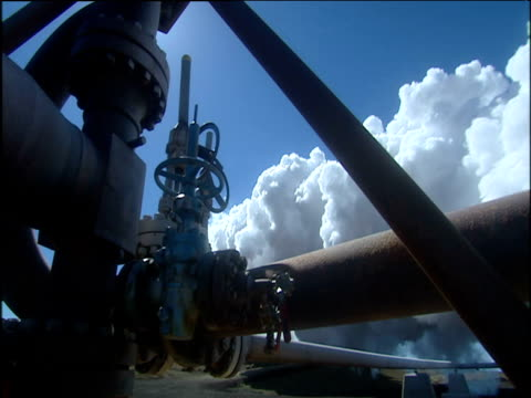 large thick industrial piping steam billows past in background under blue sky - power in nature stock videos & royalty-free footage