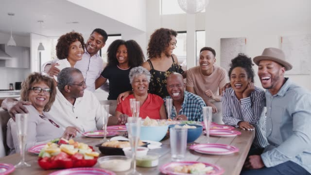 Large three generation black family group portrait at dinner table during a celebration at home