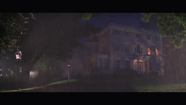WS Large three story colonial house at rainy night