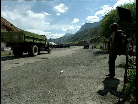 large truck pulls away along track in mountainous landscape tajikistan - ムラがある点の映像素材/bロール