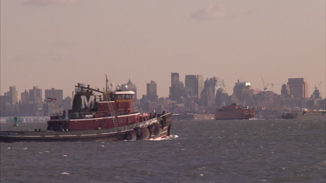 A large tugboat cruises through a harbor near New York City.