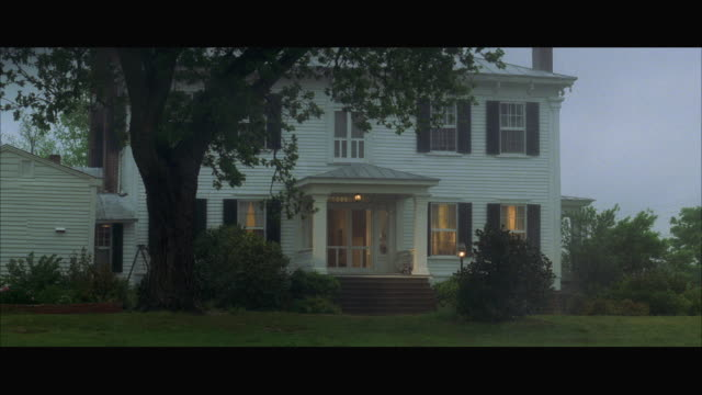 vidéos et rushes de ms large two story wooden house surrounded by trees in rain and fog - loggia