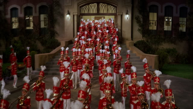 ms pan large uniformed march band leaving from entrance of public building - marching band stock videos & royalty-free footage