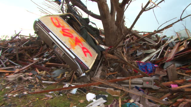 stockvideo's en b-roll-footage met a large vehicle is launched into a tree in the town of moore oklahoma in the aftermath of the devastating ef5 tornado in may 2013 - 2013