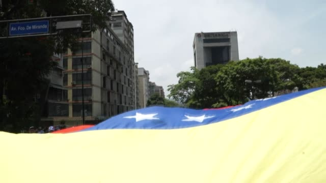 Large Venezuelan flag being carried by opposition leader Juan Guaido supporters during protest march in Caracas