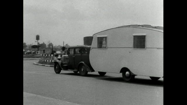 large vintage car towing caravan on urban road in uk; 1950 - moving past stock videos & royalty-free footage