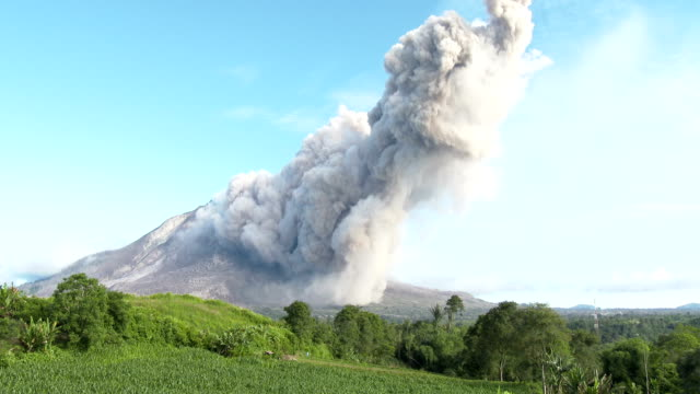 a large volcanic ash cloud drifts from sinabung volcano in sumatra indonesia during an eruption on 19th june 2015 - pyroklastischer strom stock-videos und b-roll-filmmaterial